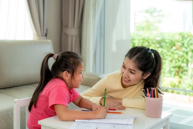 Asian mother playing with her daughter drawing together with color pencils at table in living room at home.
