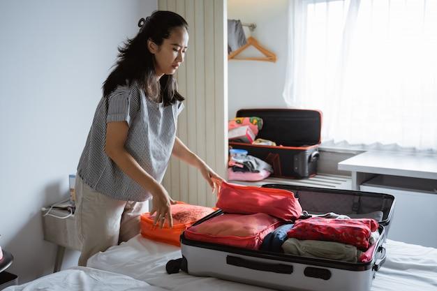 アジアの母は服とバッグを準備します