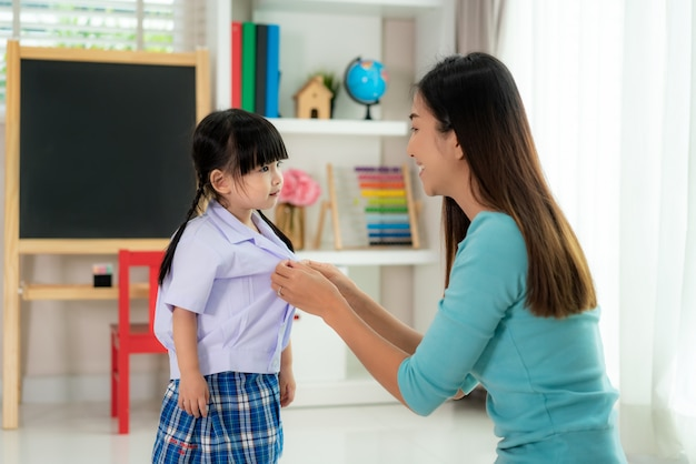 Asian mother preparing kindergarten student uniform