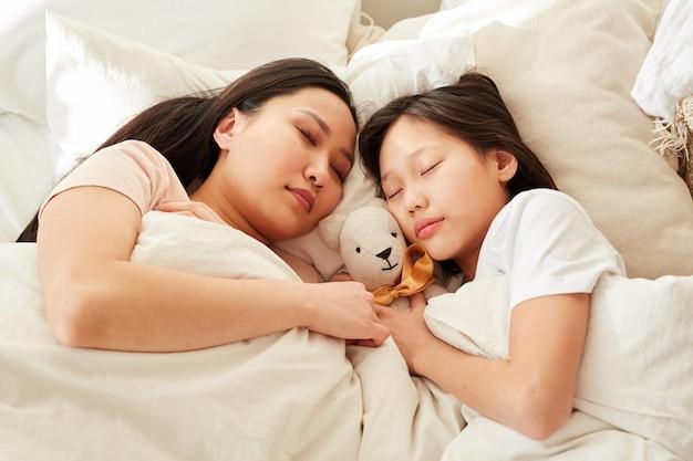 Азиатская мать спит вместе со своей дочерью в постели в спальне