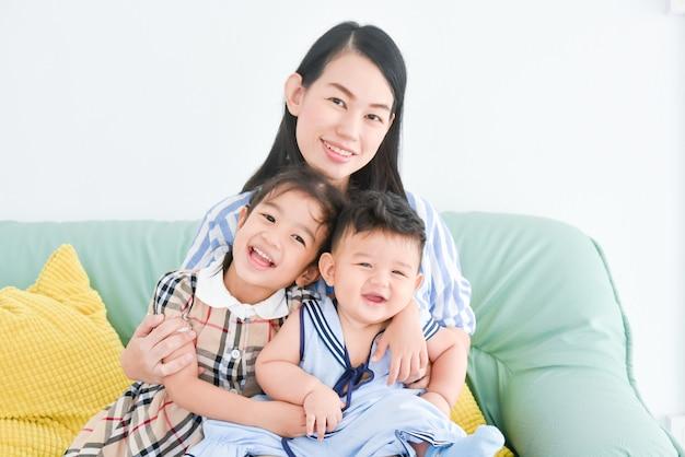 아시아 어머니는 그녀의 작은 아이를 잡고 그녀의 딸을 안고있는 동안 미소 짓는다. 아이들과 함께 행복 한 어머니입니다.