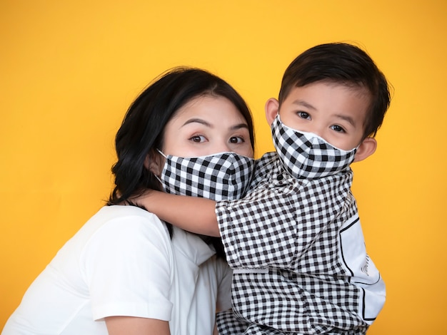 Asian mother and son are showing love and wear mask