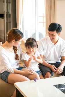 아시아 어머니는 집에서 사랑스러운 딸 손톱을 칠하기 위해 함께 행복한 가족 시간을 보냅니다.