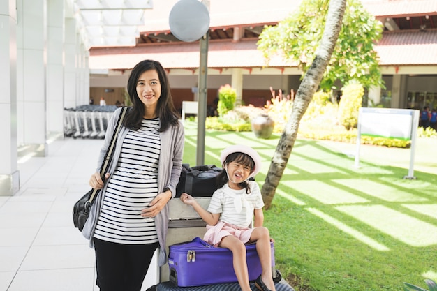 Asian mother stood carrying a bag next to her daughter sitting on a suitcase
