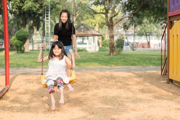 Asian mother swinging swing for her daughter, cute girl is so fun and happiness in playground, happy family time
