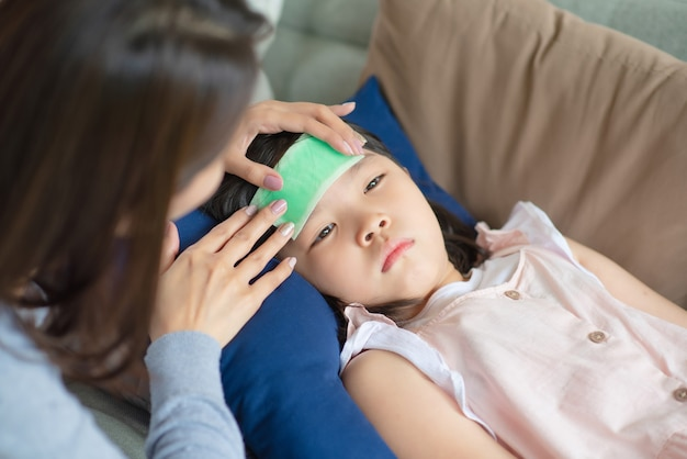 Asian mother take care of her kid which got fever and illness at home.