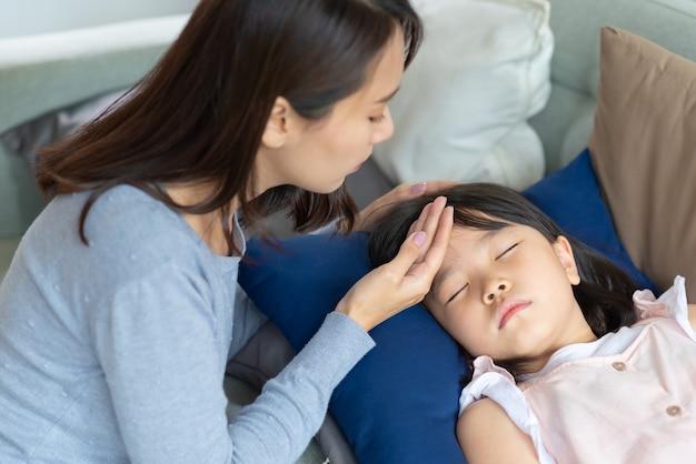 アジア人の母親は、家で熱と病気にかかった子供の世話をします。