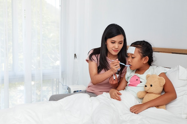 Asian mother take care sick daughter on bed