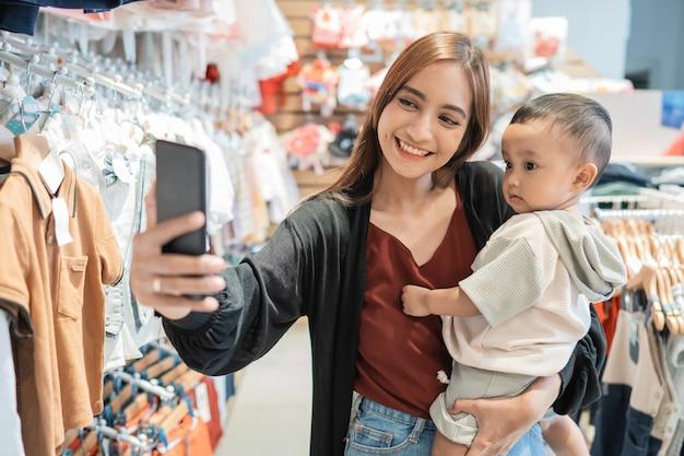 アジア人の母親がモールで買い物をしながら息子と一緒に自分撮りをする