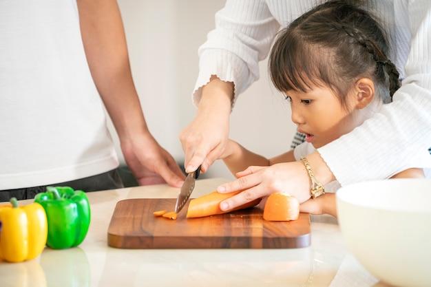 アジアの母親が娘のスライド野菜を教え、夕食、アジアの家族の概念のための食糧を準備します