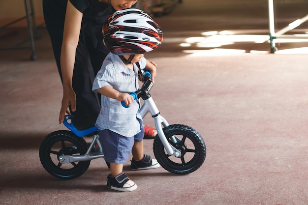 Asian mother teach her son to play baby balance bike