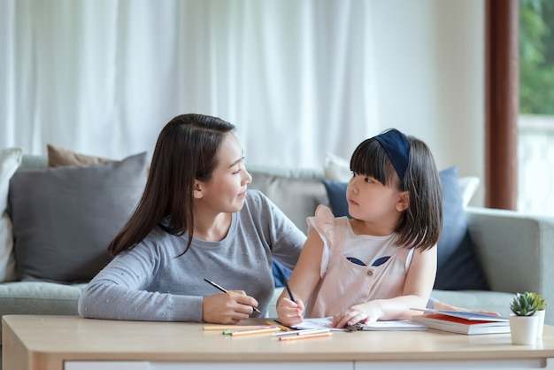 Asian mother teaching her cute kid daughter to studying in living room at home