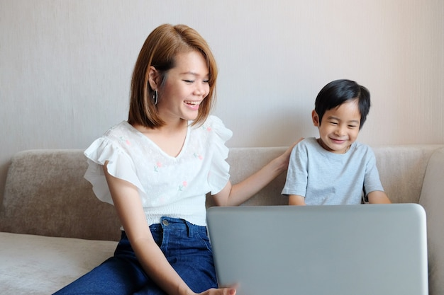 Asian mother teaching her son for use laptop computer