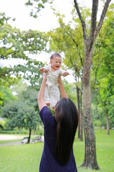 Asian mother throws up happy infant baby boy in arms at garden.