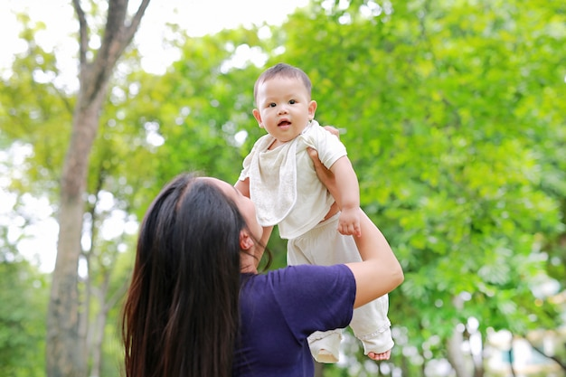 Asian mother throws up her infant in arms at garden.