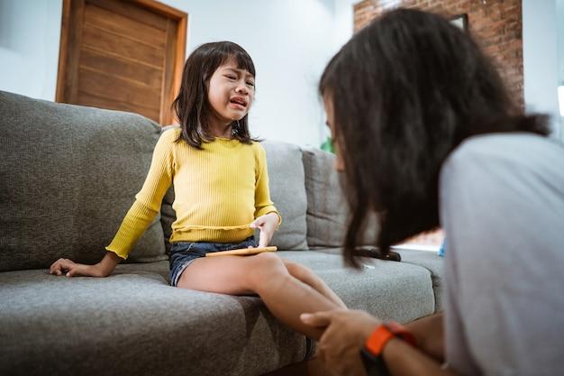 Азиатская мать лечит раненую дочь антисептиком дома