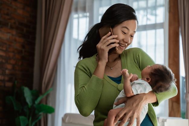 小さな娘を保持しているときにスマートフォンを使用してアジアの母