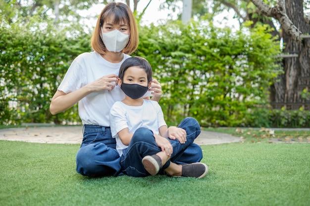 Азиатская мать носит маску для лица своему сыну мальчику в домашнем саду