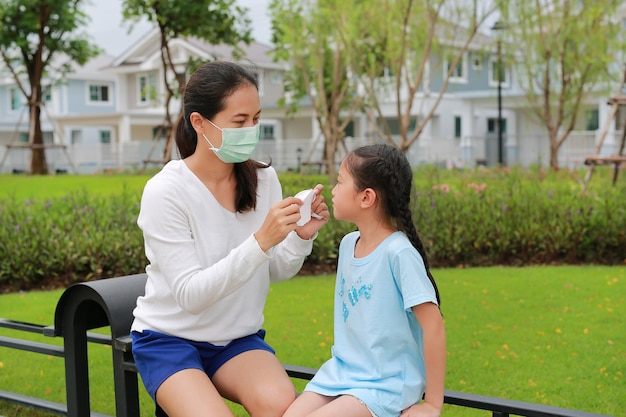 Азиатская мать в защитных масках для дочери в сквере