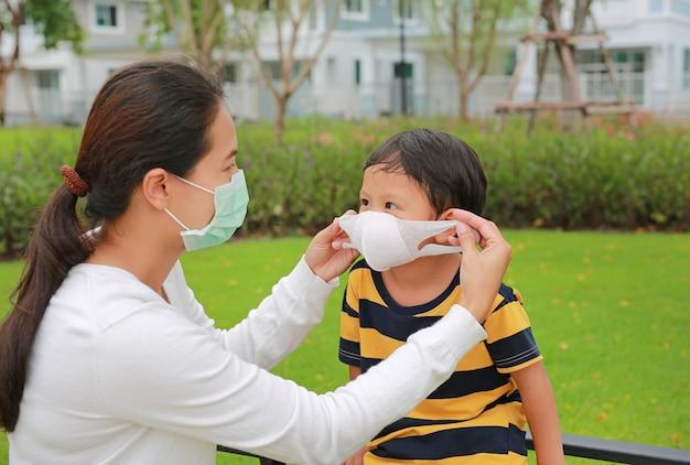 コロナウイルスとインフルエンザの流行中に公共の庭で男の子のための保護フェイスマスクを身に着けているアジアの母親