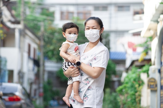 Asian mother wearing white face mask holding her little toddler baby girl who is her daughter wear baby face mask, they look at camera, covid-19 concept