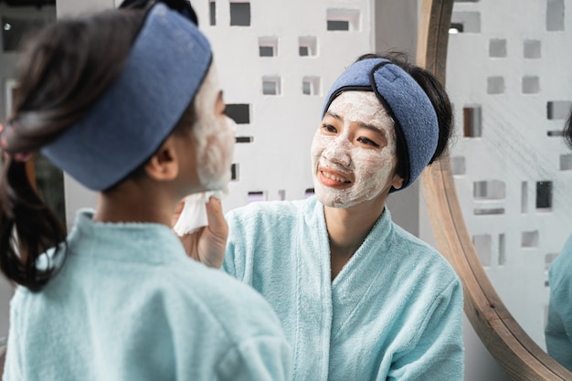 그녀의 얼굴에 크림 마스크를 쓴 아시아 어머니도 수건을 착용하면서 어린 소녀의 얼굴 마스크를 문질러