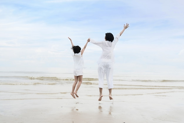 Asian mother with daughter holding hands, having fun and jumping on beach.
