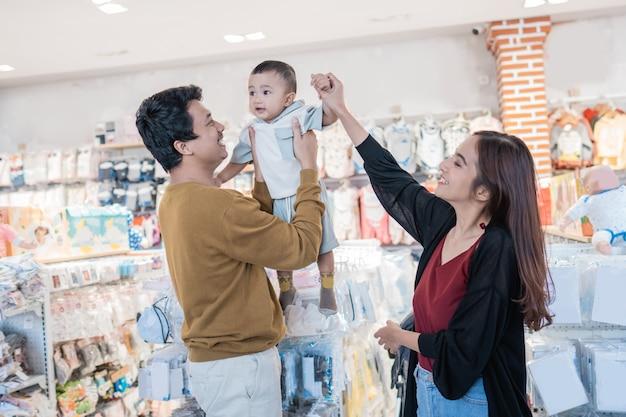 ベビーショップで買い物をしている彼女の幼児の男の子とアジアの母親