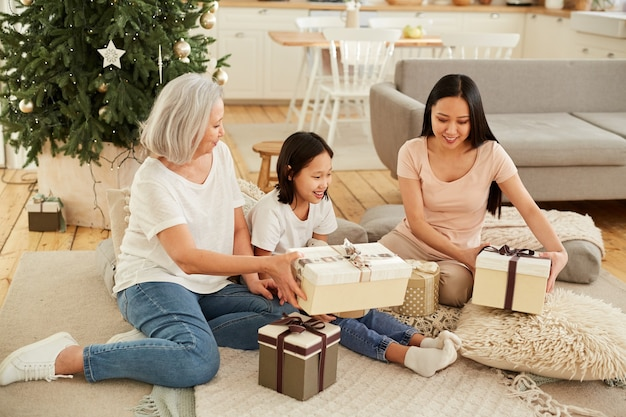 Asian mother with her two daughters sitting on the floor near christmas tree and opening presents in the room