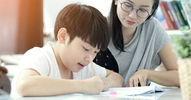 Asian mother with son doing homework in living room.