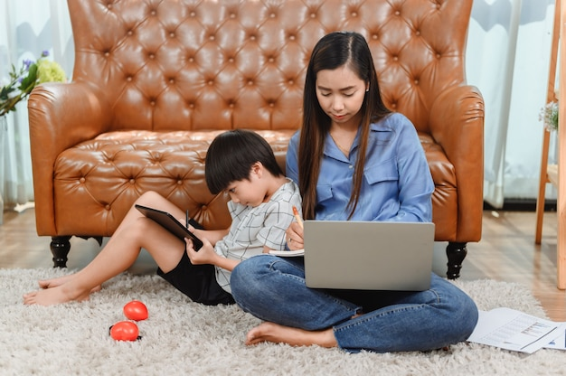 アジアの母親は家で働きます。息子と一緒にお母さん。子供のオンライン学習教育。新しい通常のライフスタイルと家族の活動。