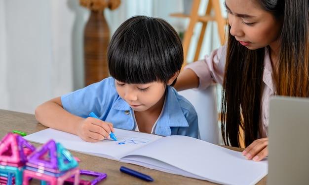 Азиатская мать работает дома вместе с сыном. мама и ребенок рисуют картину и искусство цветной живописи. образ жизни женщины и семейная активность.