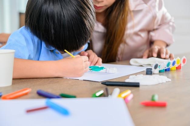 아시아 어머니는 아들과 함께 집에서 일합니다. 엄마와 아이 그림과 컬러 페인팅 아트. 여성의 생활 방식과 가족 활동.
