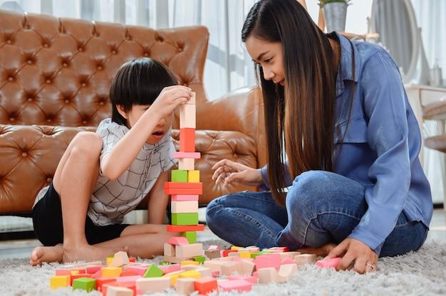 アジア人の母親は息子と一緒に家で働きます。ママと子供は色の木製ブロックを再生します。建物のおもちゃを作成する子供。女性のライフスタイルと家族の活動。