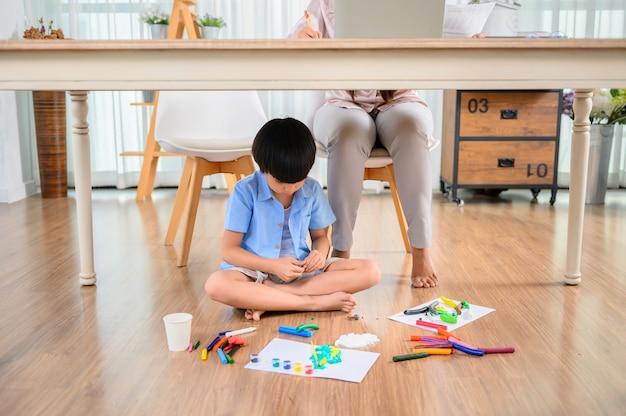 아시아 어머니는 아들과 함께 집에서 일합니다. 엄마는 온라인으로 일하고 아이는 탁자 아래에서 반죽을 합니다. 여성의 생활 방식과 가족 활동.