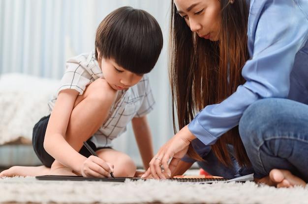 アジア人の母親は息子と一緒に家で働きます。オンライン学習教育のために子供を教えるお母さん。新しい通常のライフスタイルと家族の活動。