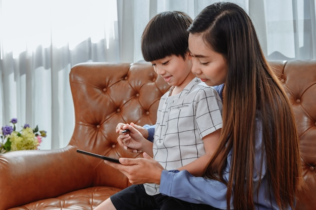 아시아 어머니는 아들과 함께 집에서 일합니다. 온라인 학습 교육을 위해 아이를 가르치는 엄마. 새로운 일상 생활과 가족 활동.