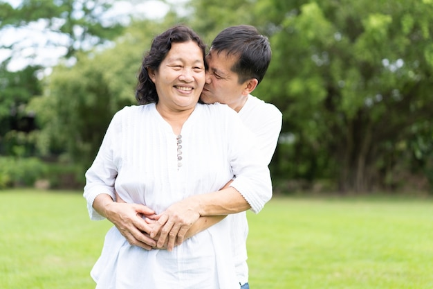 Asian mother and young son are standing and kissing together in the park