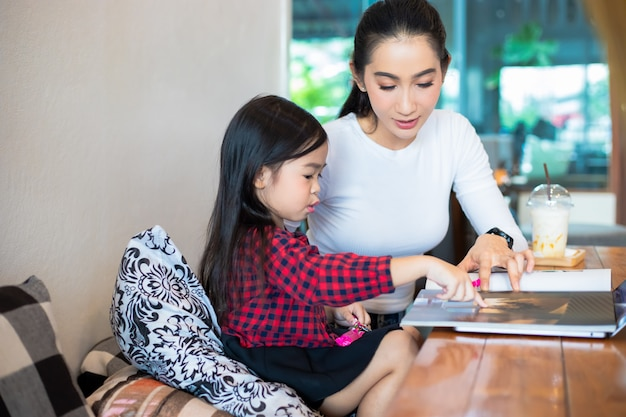 Asian mothers are teaching their daughters to read a book and use notebooks and technology for online learning during school holidays at home. educational concepts and activities of the family