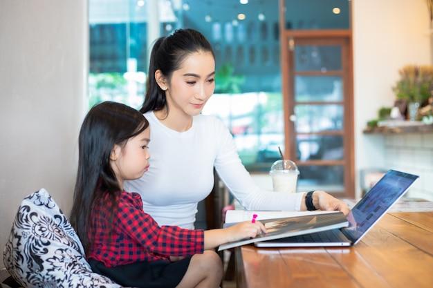 Азиатские мамы учат своих дочерей читать книги и использовать тетради и технологии для онлайн-обучения во время школьных каникул дома. образовательные концепции и деятельность семьи