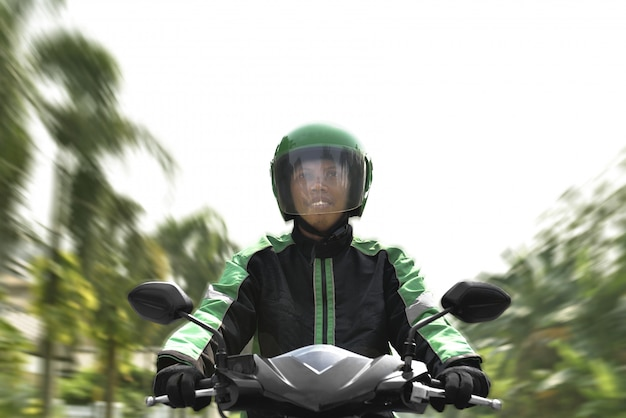Asian motorcycle taxi rider rushing