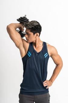 アジアの筋肉マンが上腕三頭筋のエネルギーでダンベルの重りを持ち上げる