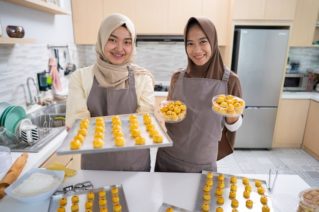 Asian muslim beautiful woman with hijab making nastar cake. tray full of homemade snack