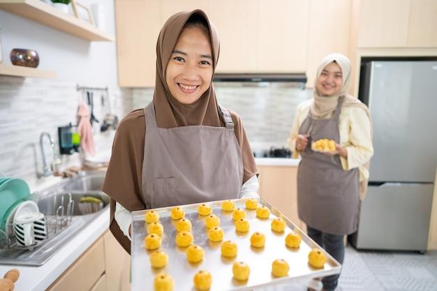 Nastar 케이크를 만드는 hijab와 아시아 이슬람 아름 다운 여자. 홈 메이드 스낵이 가득한 트레이