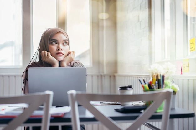 Asian muslim business woman brown hijab working at home looking outside.