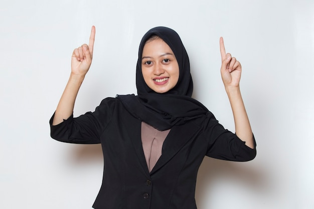 Asian muslim business woman pointing fingers to different directions copy space for advertisement