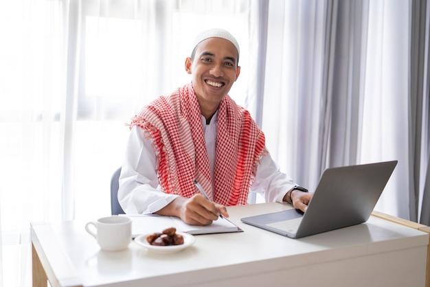 机の上に座ってラップトップを使用して作業しているアジアのイスラム教徒のビジネスマン