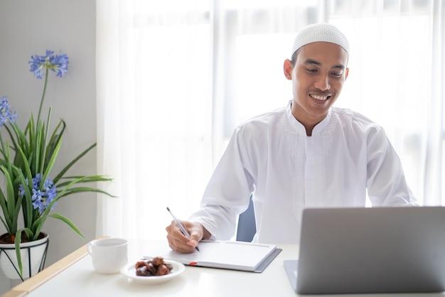 책상에 앉아있는 동안 노트북을 사용하여 작업하는 아시아 이슬람 사업가