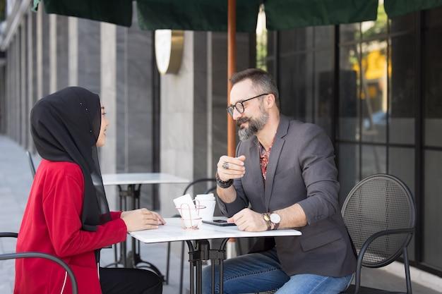Asian muslim businesswoman in coffee shop talking to customer or boy friend