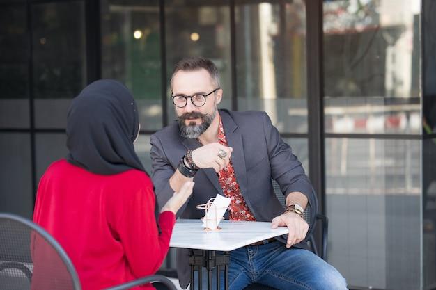 顧客またはボーイフレンドと話しているコーヒーショップでアジアのイスラム教徒の実業家